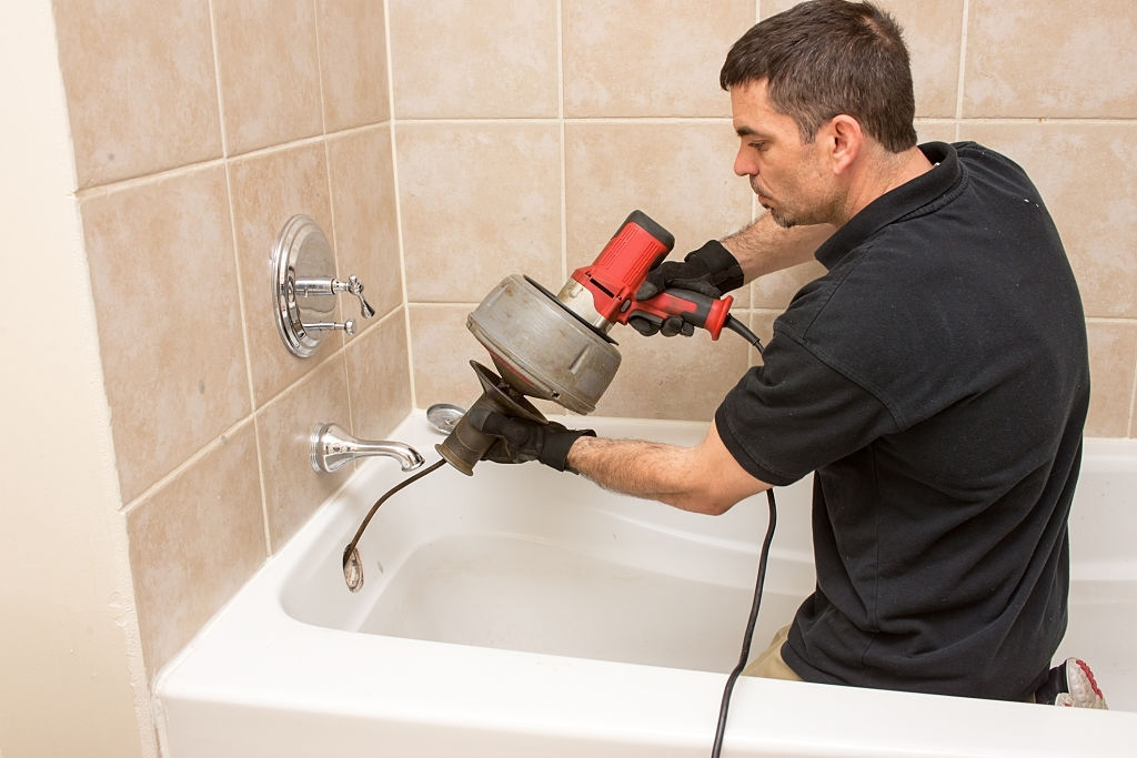 electric drain auger being used by a plumber